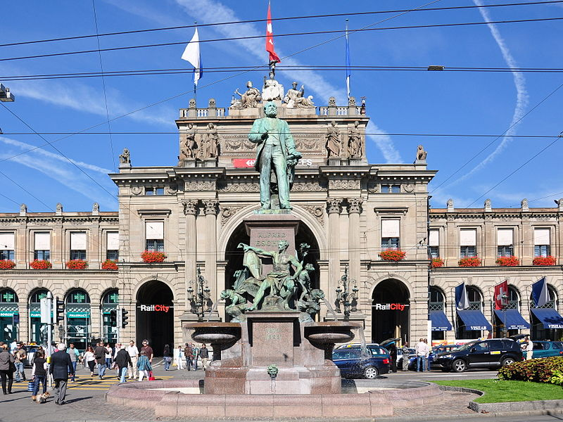 Alfred Escher monumental fountain, sculpted by Richard Kissling, on Bahnhofplatz situated at Hauptbahnhof in Zürich (Switzerland)  Image from Wikimedia Commons - by Roland Zh.